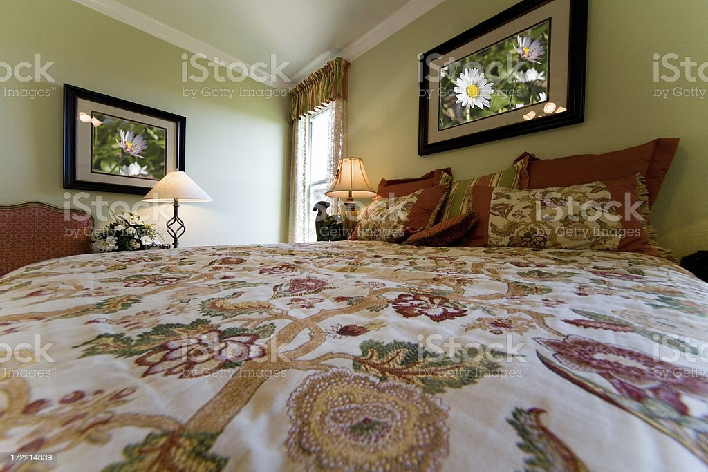 Surface level view of a floral bedspread in cozy bedroom. royalty-free stock photo