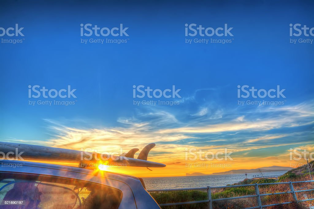 surfboard at sunset stock photo