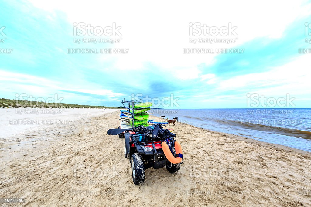Surfboards stacked on quad bike on the beach stock photo