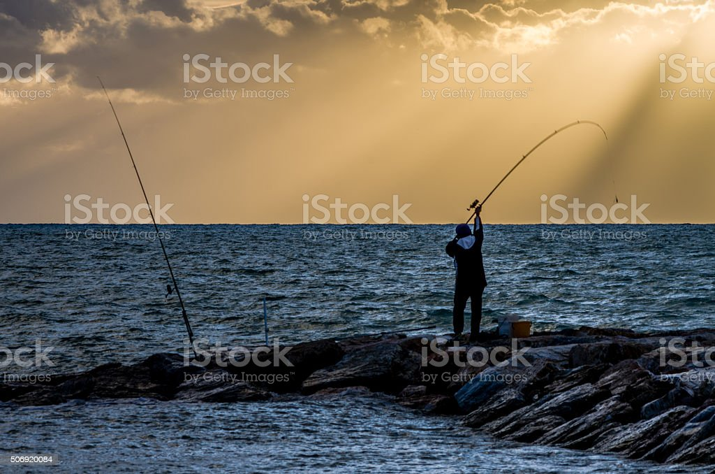 Surfcaster in the sunset stock photo