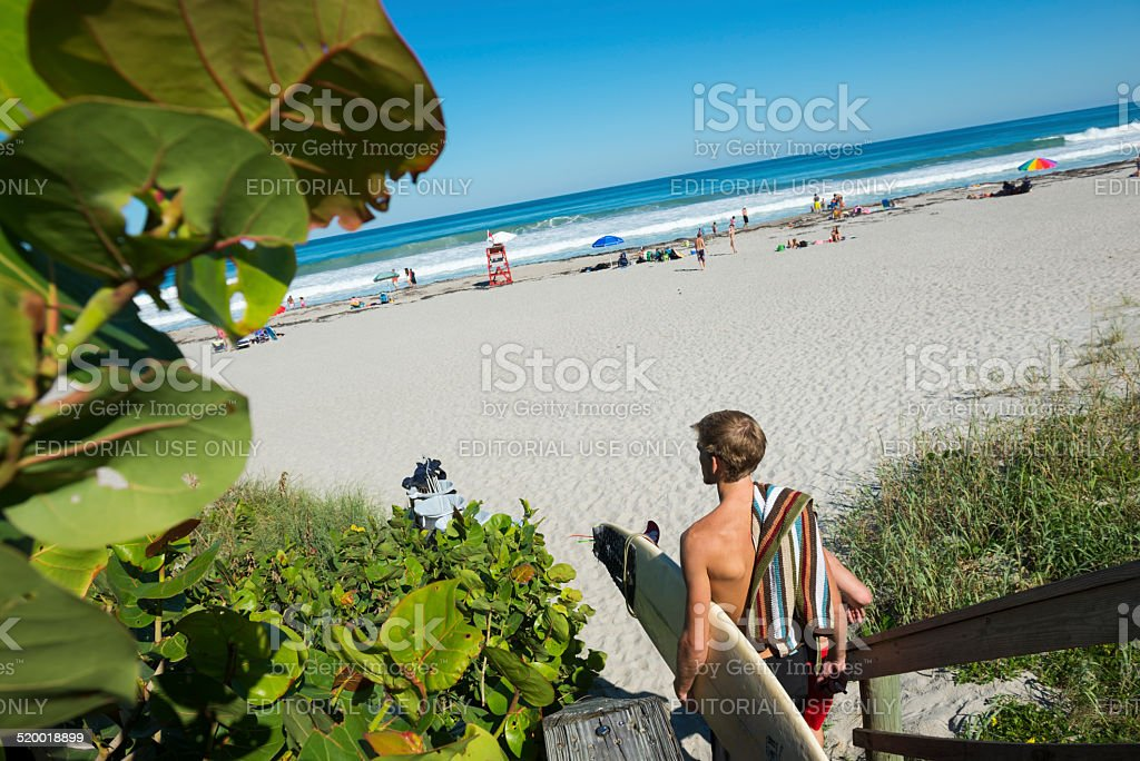 Surfer arriving at the beach stock photo
