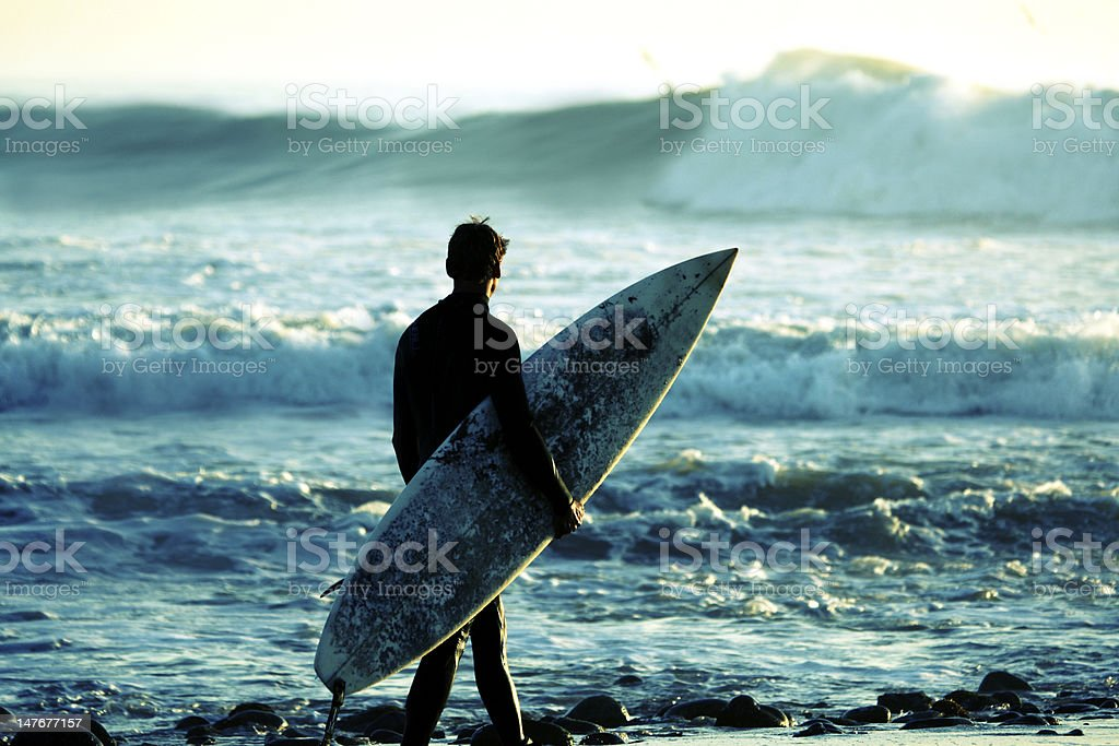 Surfer at dusk stock photo