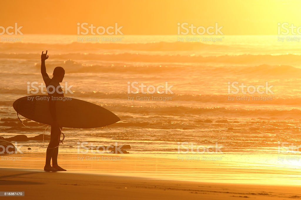 Surfer at sunset stock photo
