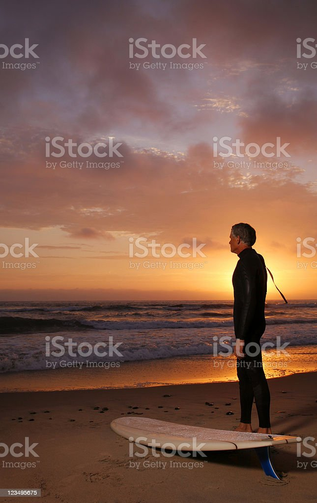 Surfer at Sunset Pondering Retirement royalty-free stock photo