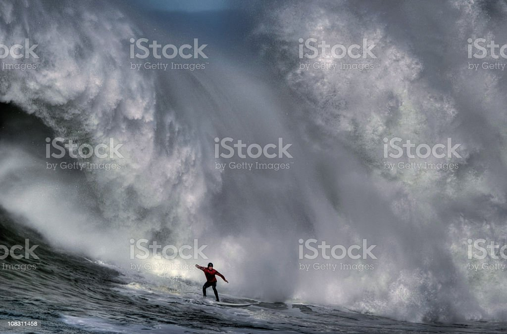 Surfer at the bottom of a huge crashing wave  stock photo