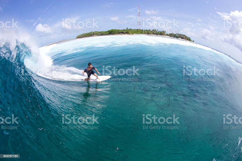 Surfer bottom turns a tropical wave stock photo