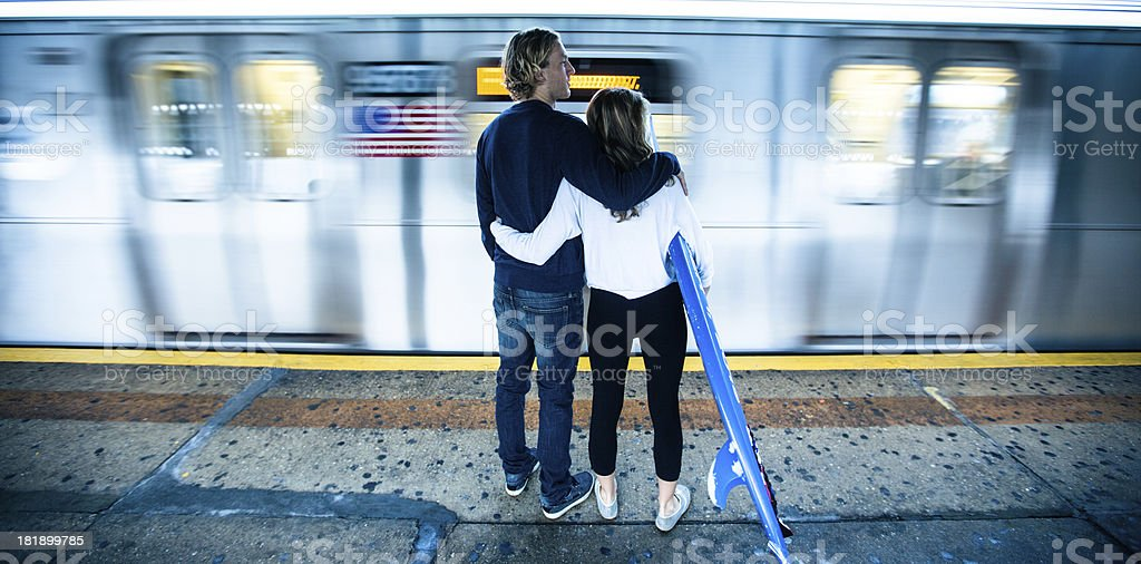 Surfer couple waiting for the subway in New York stock photo