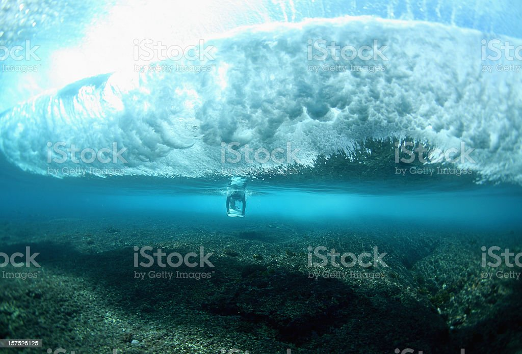 surfer dives underneath a breaking wave royalty-free stock photo