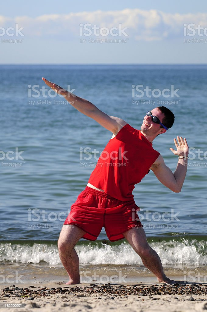 Surfer dude exercising on the beach in red swim suit. stock photo