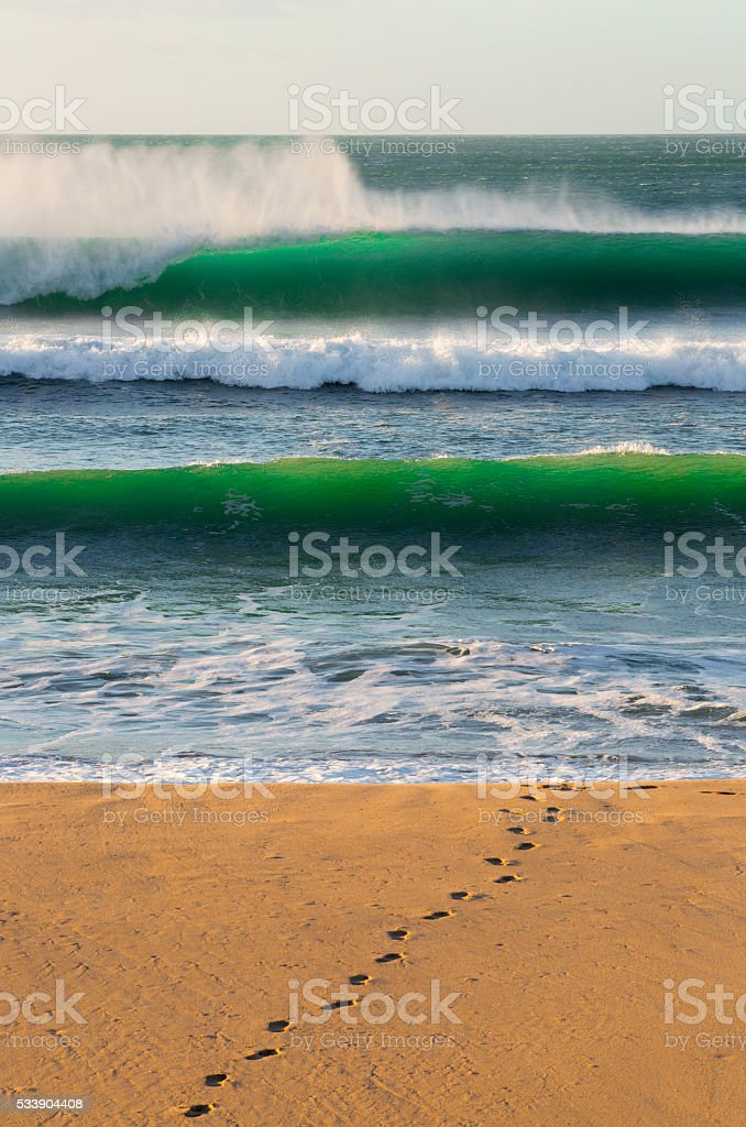 Surfer footprints on sandy beach with green waves crashing behind stock photo