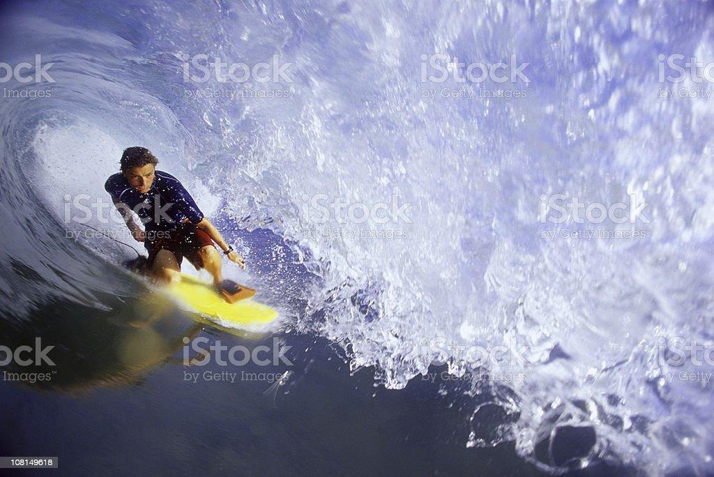 Surfer getting barreled on ocean wave stock photo