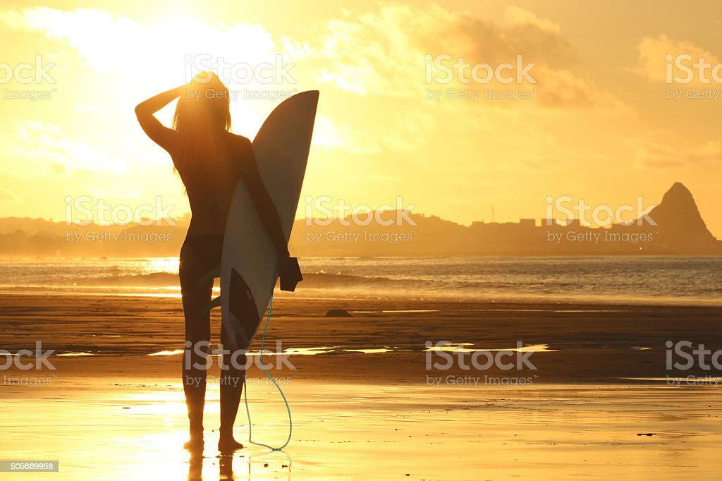 Surfer girl at sunset stock photo