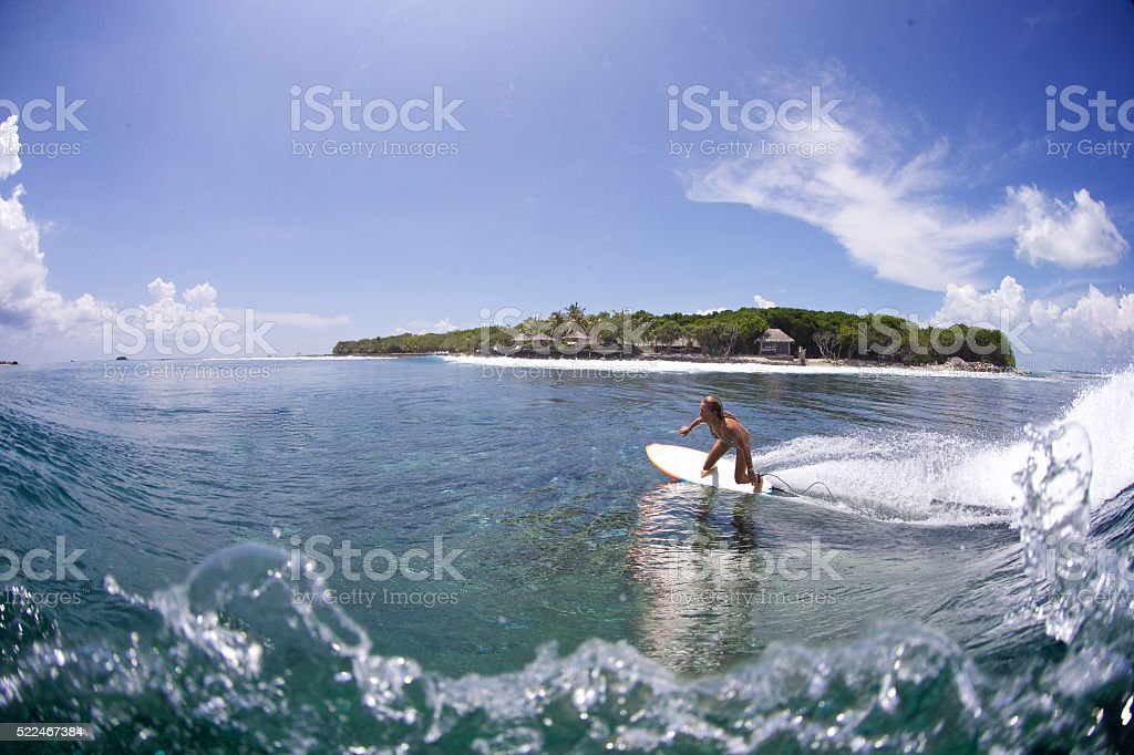 Surfer girl bottom turns on a wave stock photo