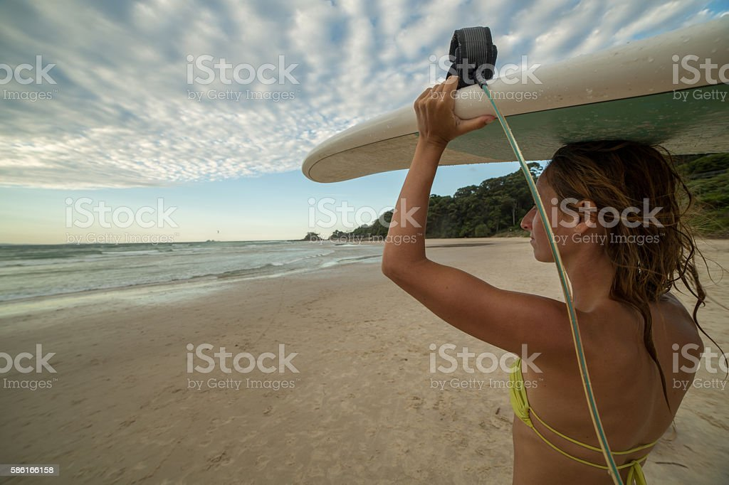 Surfer girl carrying surfboard to the ocean stock photo