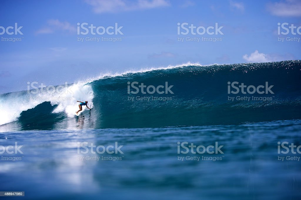 Surfer girl drops into a big perfect left wave stock photo