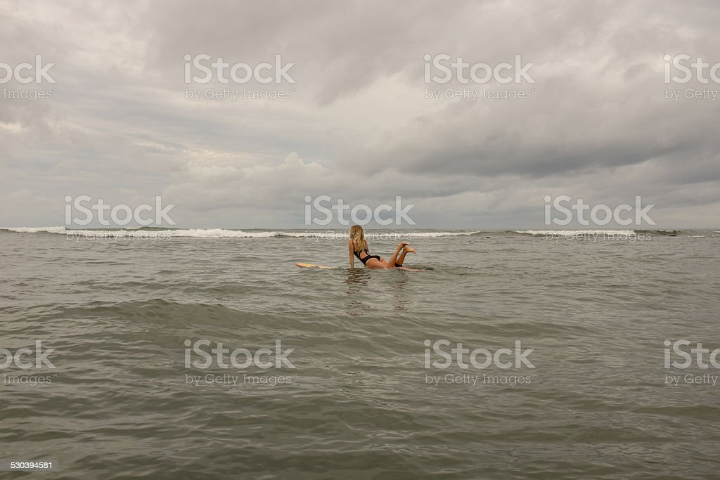 Surfer girl looking for waves stock photo