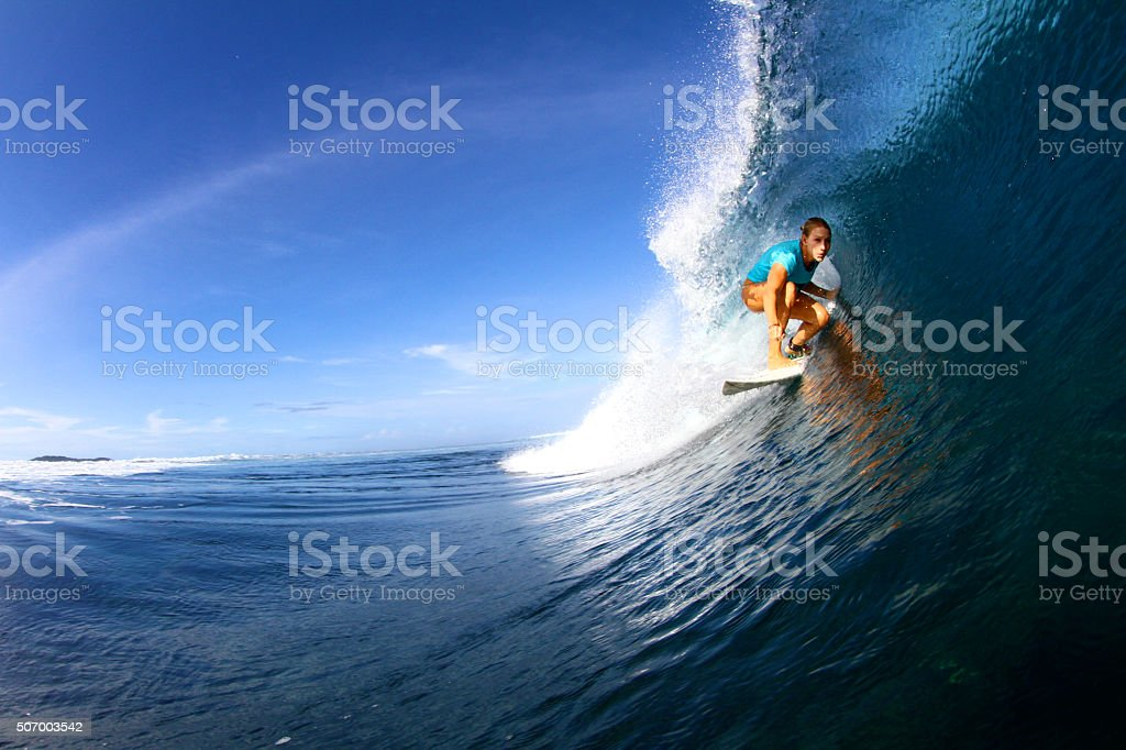 Surfer girl pulls into a barrel stock photo