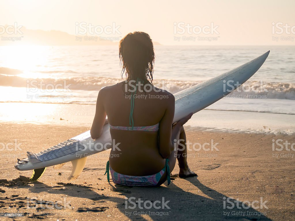 Surfer girl relaxing on the sand stock photo