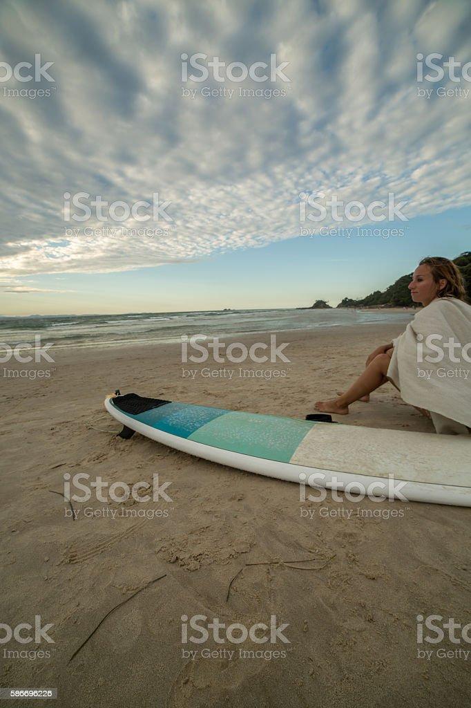Surfer girl resting on beach stock photo