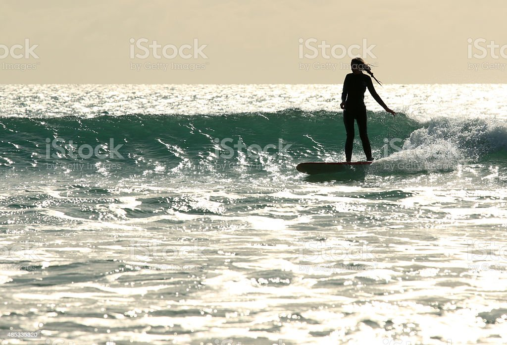 Surfer girl rides wave stock photo