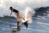 Surfer girl riding a wave at Seal Beach, CA