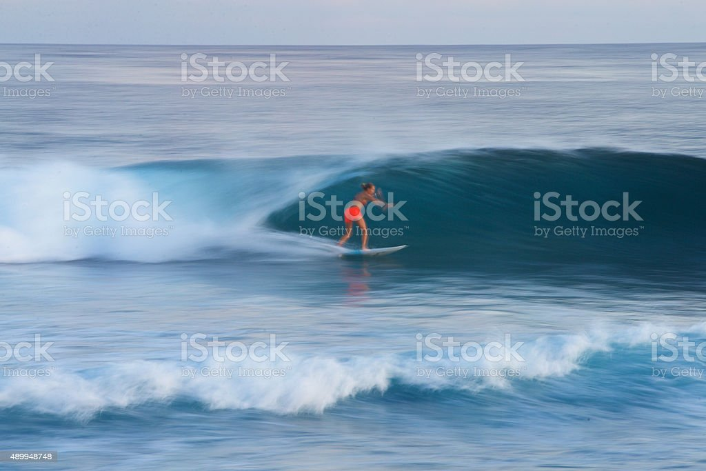 Surfer girl speeds along a perfect wave stock photo