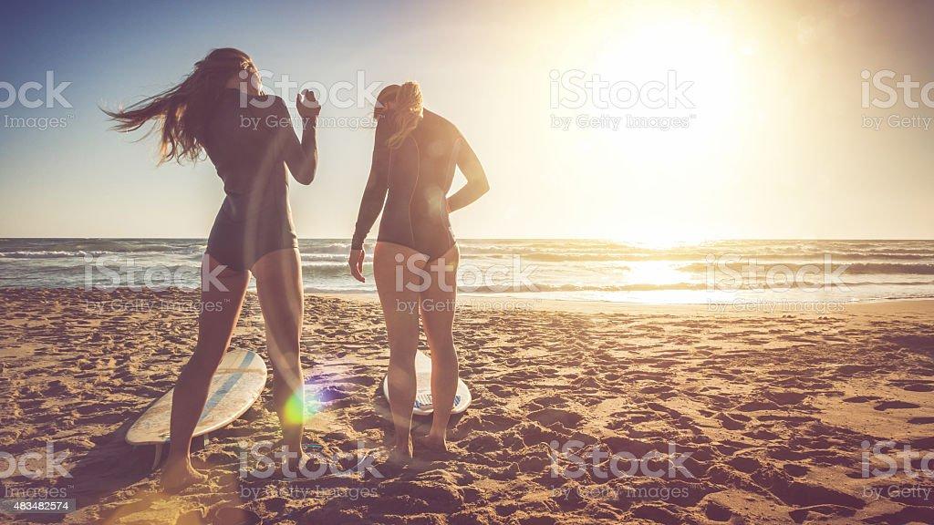 Surfer girls at sea stock photo