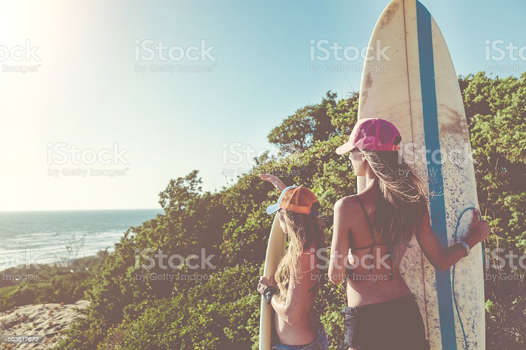 Surfer girls going to the sea stock photo