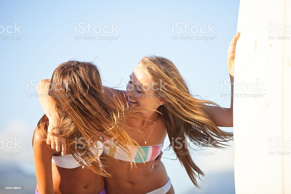 Surfer girls hugging and laughing on the beach in summer royalty-free stock photo