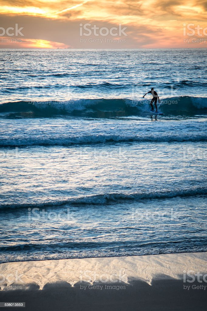 surfer greeting in a sunset, vertical format with sea waves stock photo