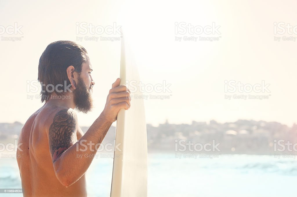Surfer holding his surfboard at the beach stock photo