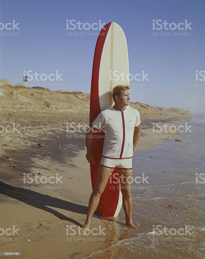 Surfer holding surfboard on beach royalty-free stock photo