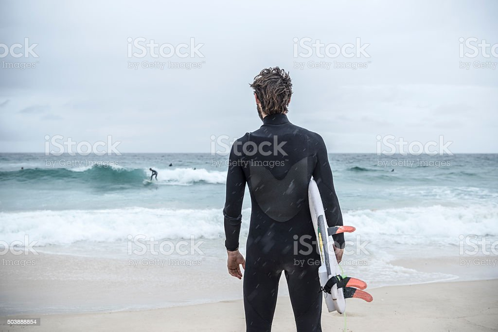 Surfer holding surfboard on Bondi Beach, rear view stock photo