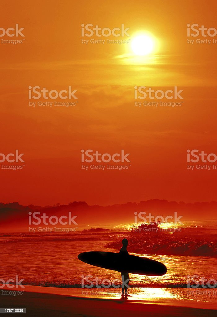 Surfer in tropical location with sunset stock photo