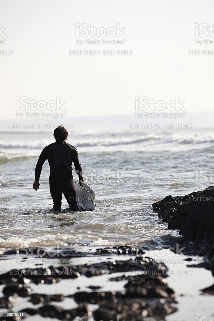 Surfer in wetsuit carrying board into sea stock photo