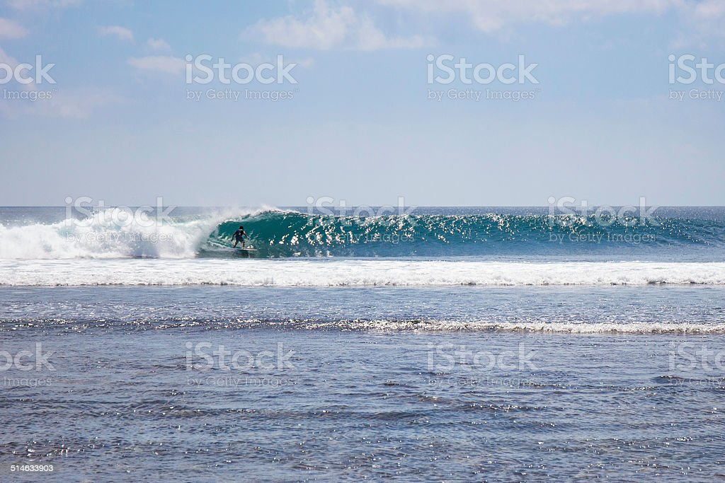 Surfer is riding a big wave in Bali island stock photo