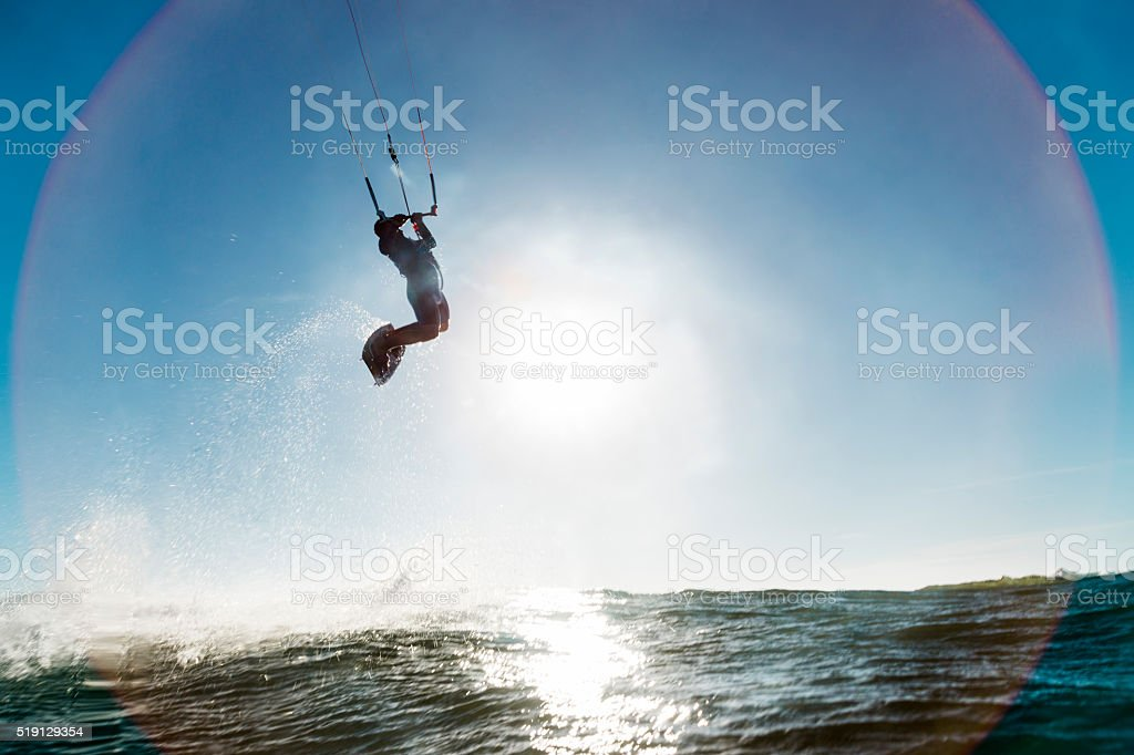 Surfer jumping in front of the sun stock photo