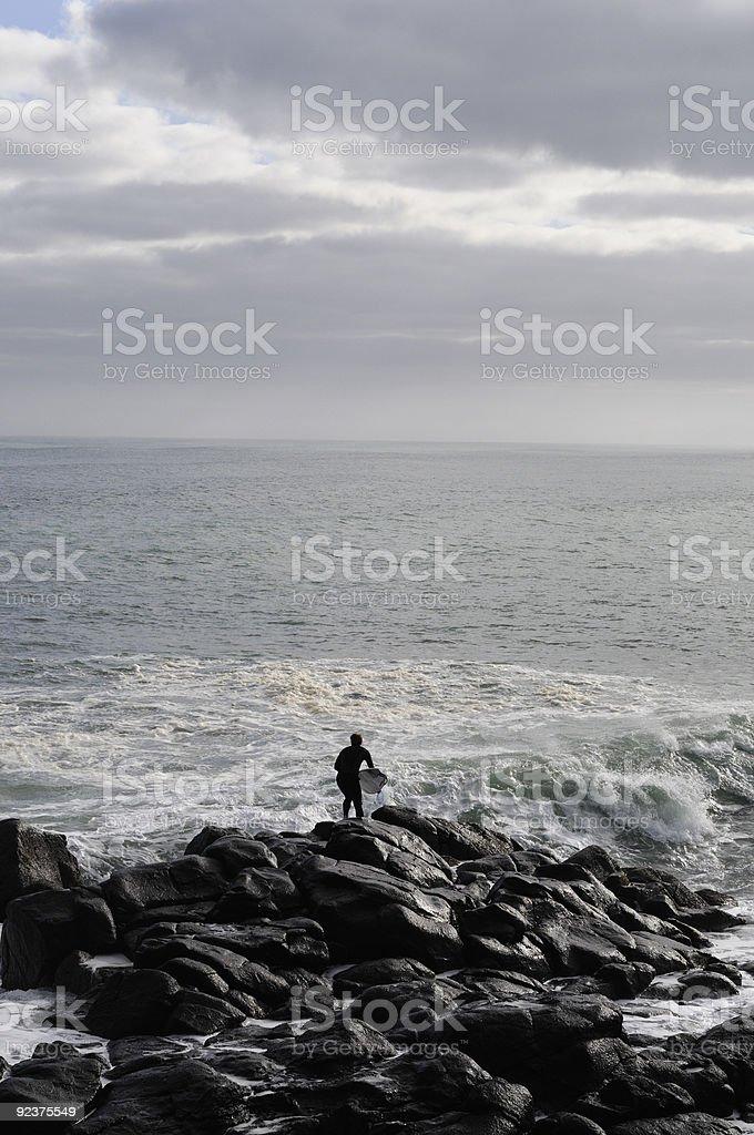 surfer jumping of rocks stock photo