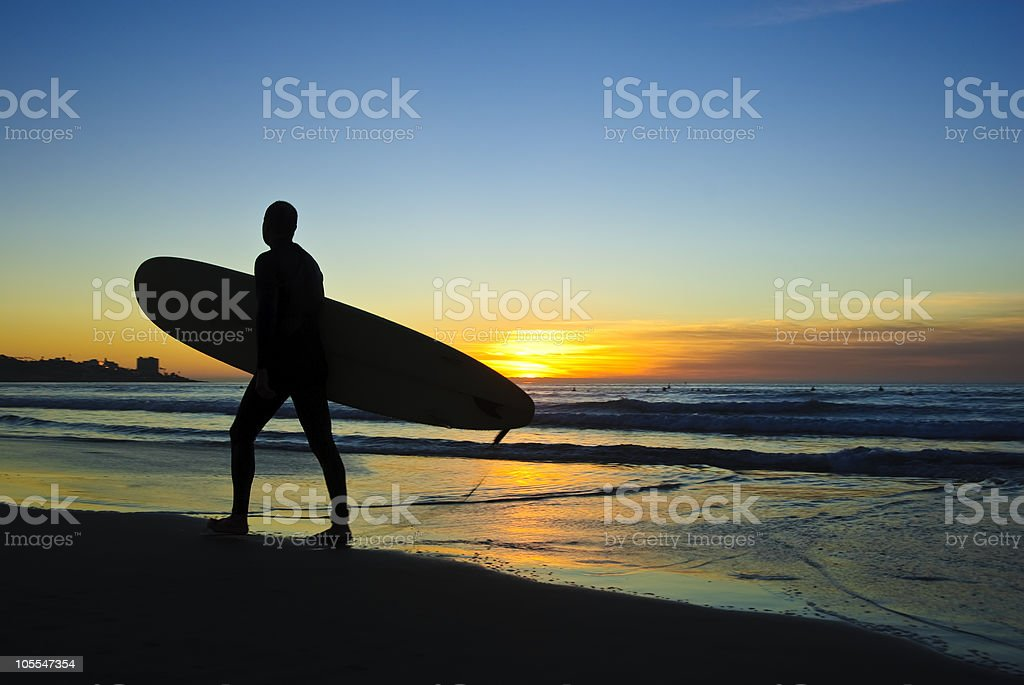 A surfer leaving the beach at sunset stock photo