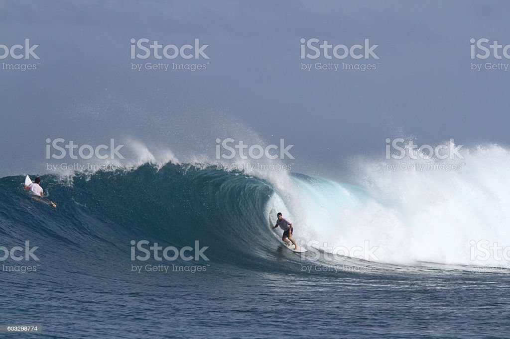 Surfer on a big barreling wave stock photo