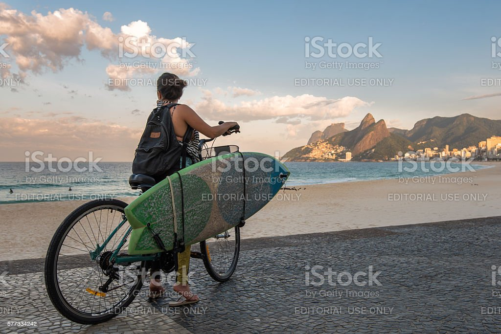 Surfer on a Bike at the Beach stock photo