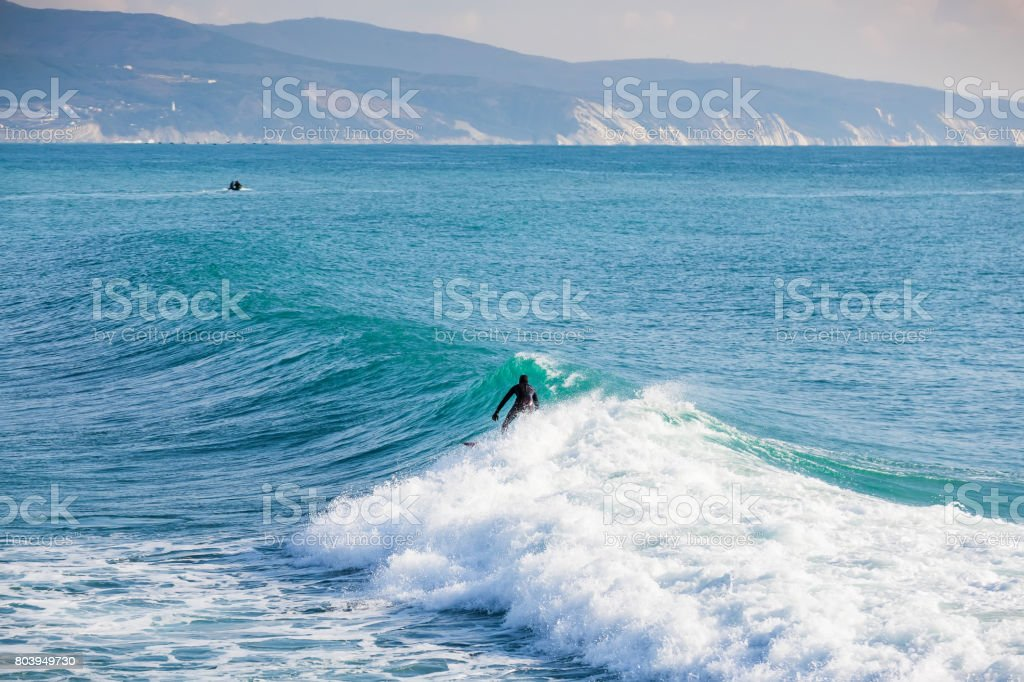 Surfer on blue wave in ocean and mountins stock photo