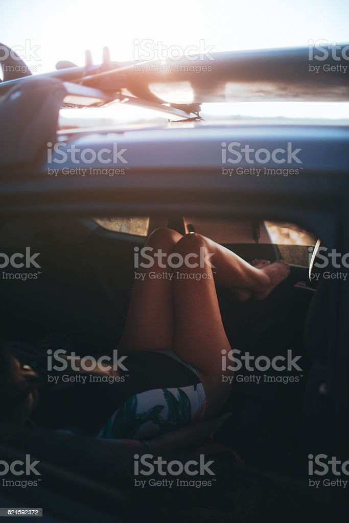 Young female surfer resting in the car during summer road trip, while...
