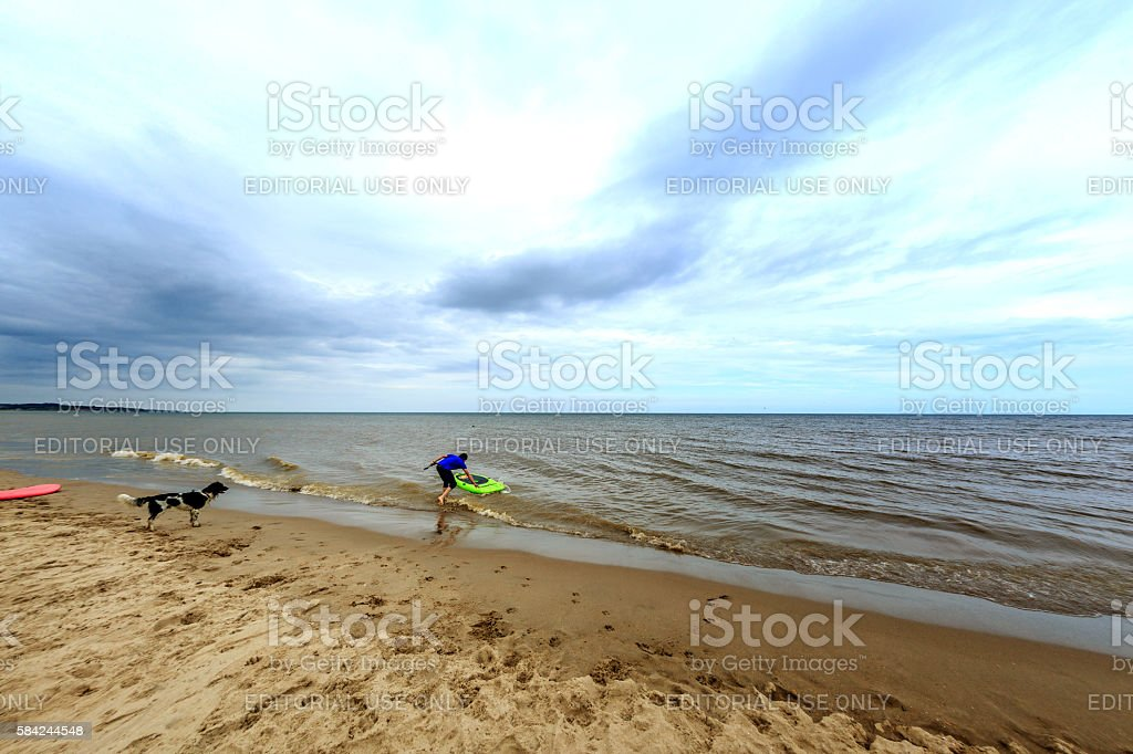 Surfer on the water and his dog on the beach stock photo