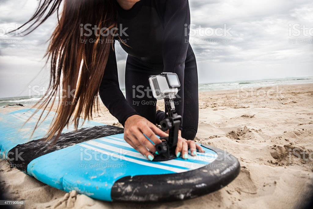 Surfer preparing on board camera on the surfboard stock photo