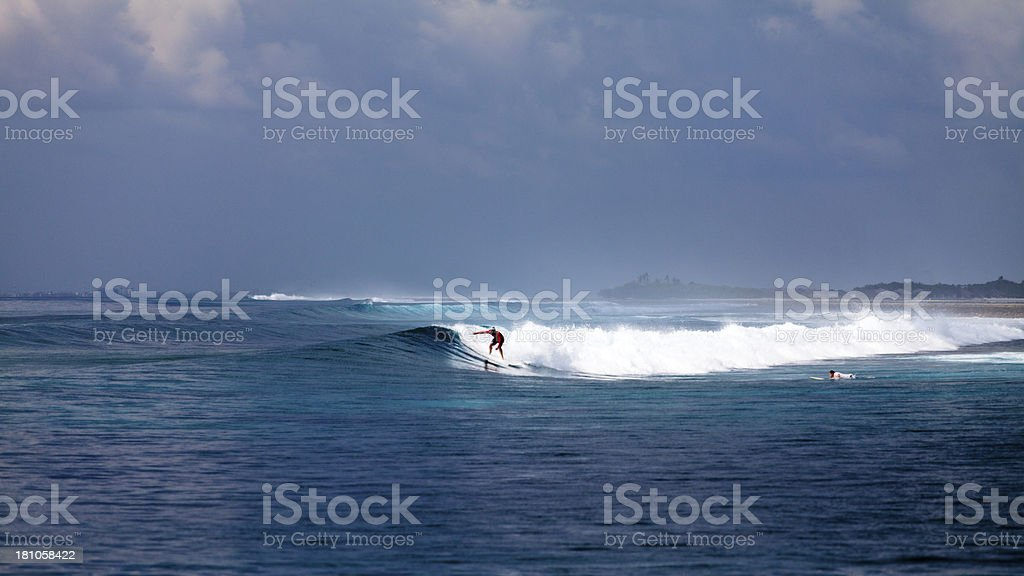 Surfer riding a wave in distance royalty-free stock photo