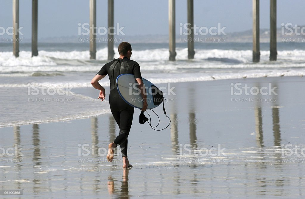 Surfer running on the beach royalty-free stock photo