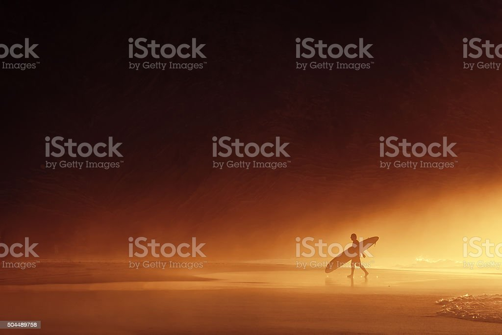 surfer silhouette at misty sunset stock photo