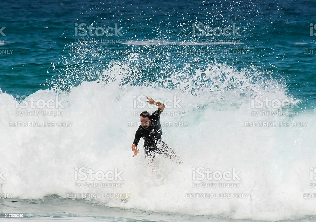 Surfer surfing at Tamarama beach stock photo