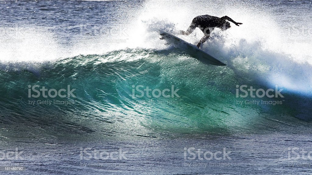 A surfer tries to stay on the surfboard while riding a wave stock photo